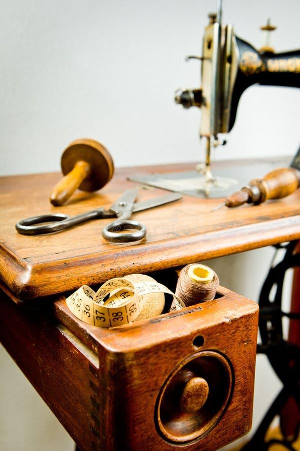 Tappningskräddares hjälpmedel på den gamla symaskinen royaltyfri bild