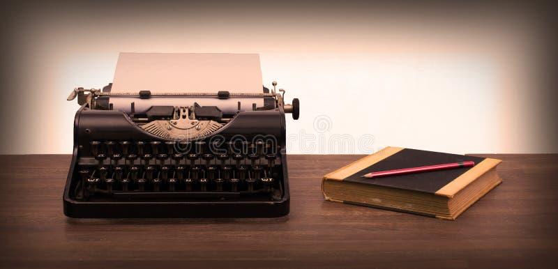Tappningskrivmaskin och gamla böcker royaltyfri fotografi