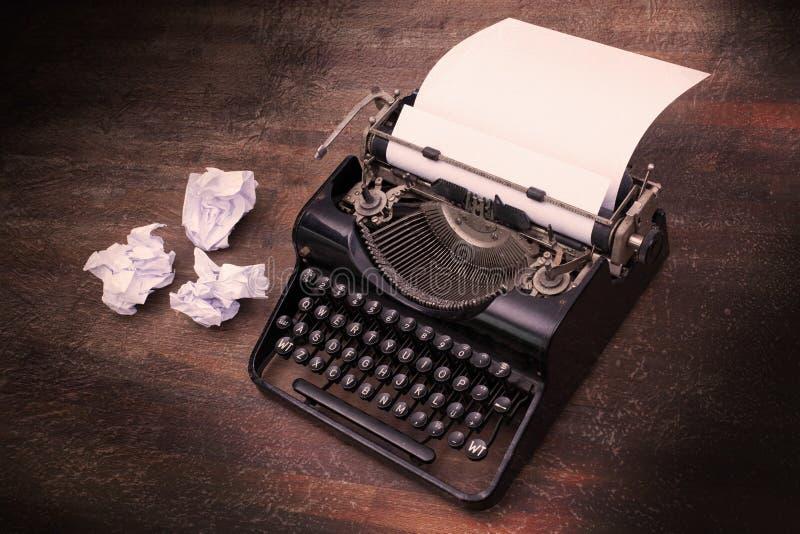 Tappningskrivmaskin och gamla böcker arkivfoto