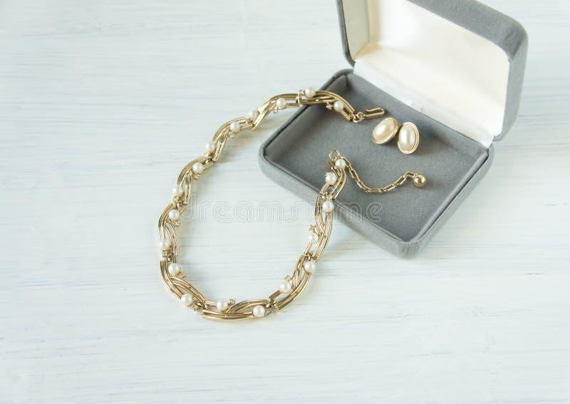 Tappningsmyckenbakgrund Härlig guld och pärlahalsband och örhängen i en gåvaask på vitt trä Lekmanna- lägenhet arkivbild