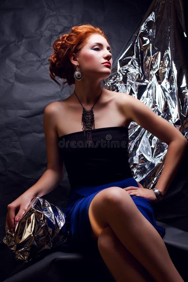 Tappningstående av den förföriska ljust rödbrun modellen med silverfolie royaltyfri foto