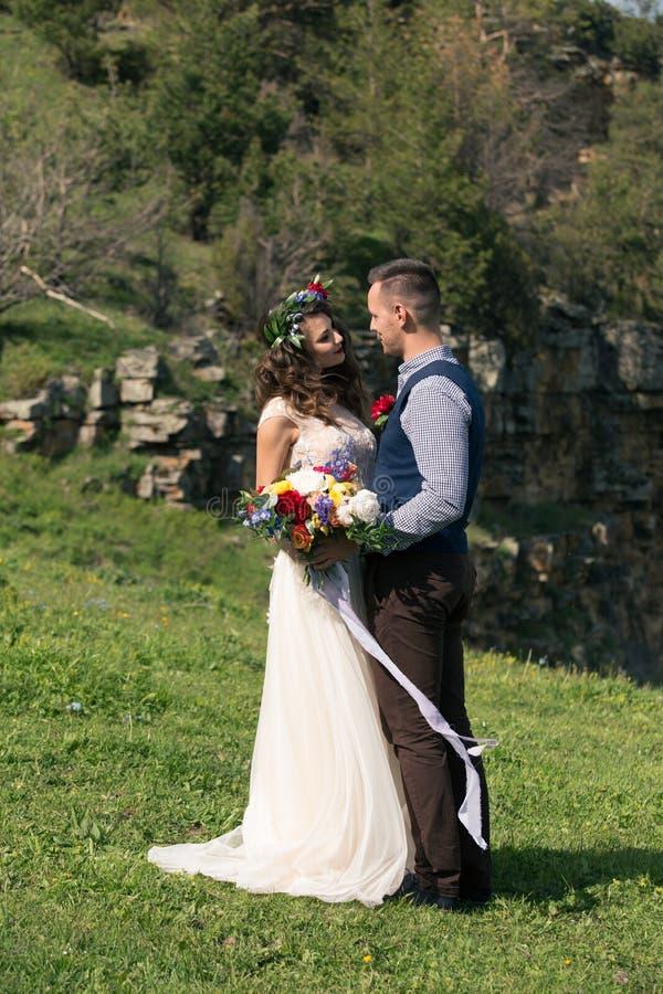 Tappningstående av ett ungt hipsterpar som poserar i bröllopfölje och klänning på solnedgången i skogen royaltyfri fotografi
