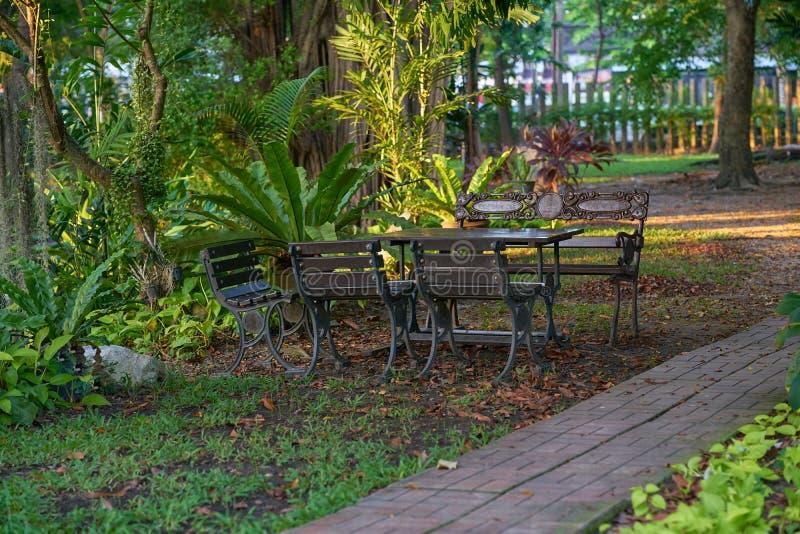 Tappningstil av tabellen och stolar i trädgård med gångbanan arkivfoton