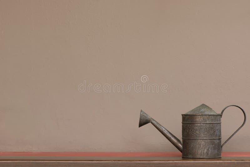 Tappningstil som bevattnar kan på hylla med brun väggbakgrund royaltyfria bilder