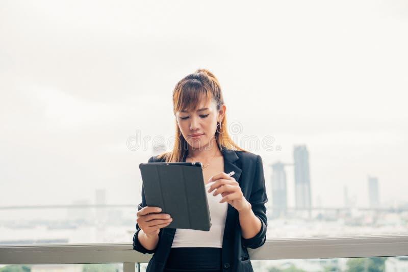 Tappningstil, ung affärskvinna med minnestavlan i kontor ag royaltyfri foto