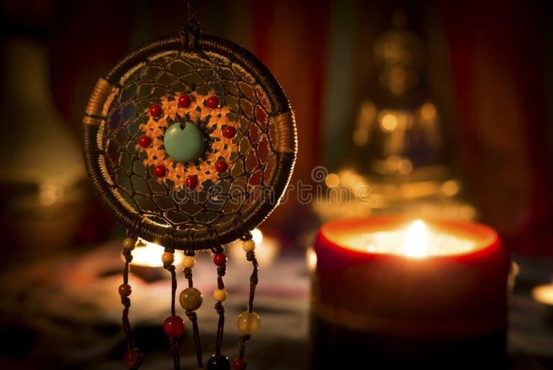 Tappningstilbilden av dreamcatcher och stearinljuset tänder med den suddiga Buddhastatyn på bakgrunden royaltyfri fotografi
