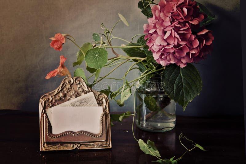 Tappningstilleben, mässingskorthållare och rosa färgvanlig hortensia royaltyfria foton