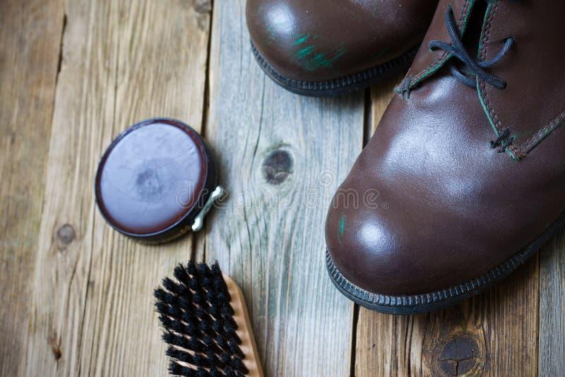 Tappningstilleben med åldriga bruntkängor, skokräm och skon borstar royaltyfri bild