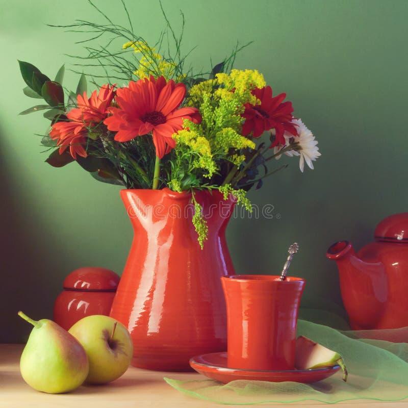 Tappningstilleben med röd bordsservis, blommar och bär frukt royaltyfri foto