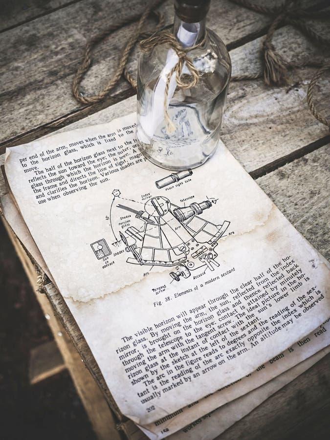 Tappningstilleben med sextantbilden i en gammal bok och en tom glasflaska med repet på åldrig träbakgrund _ arkivbild