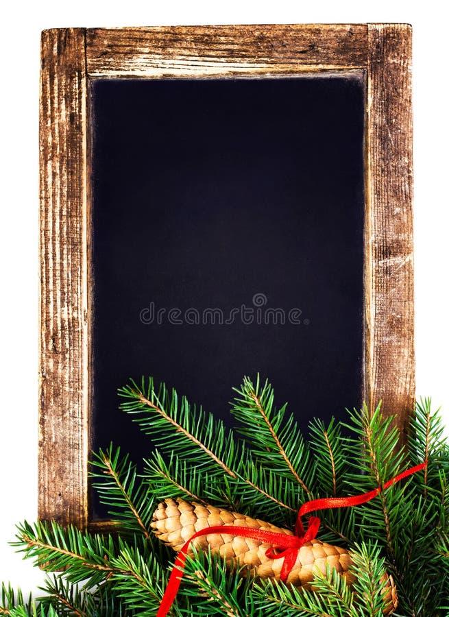 Tappningsvart tavla med julgranfilialen som isoleras på vit royaltyfri bild