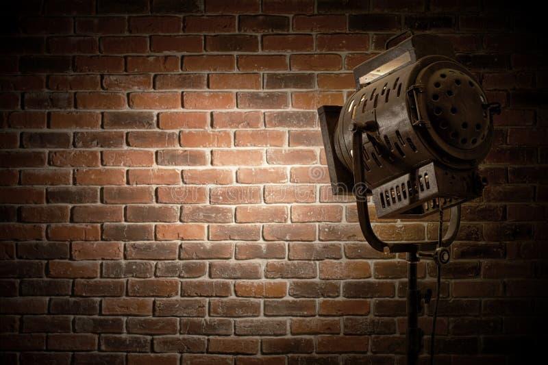 Tappningteatern/filmfläckljus fokuserade på en bakgrund för tegelstenvägg royaltyfri bild