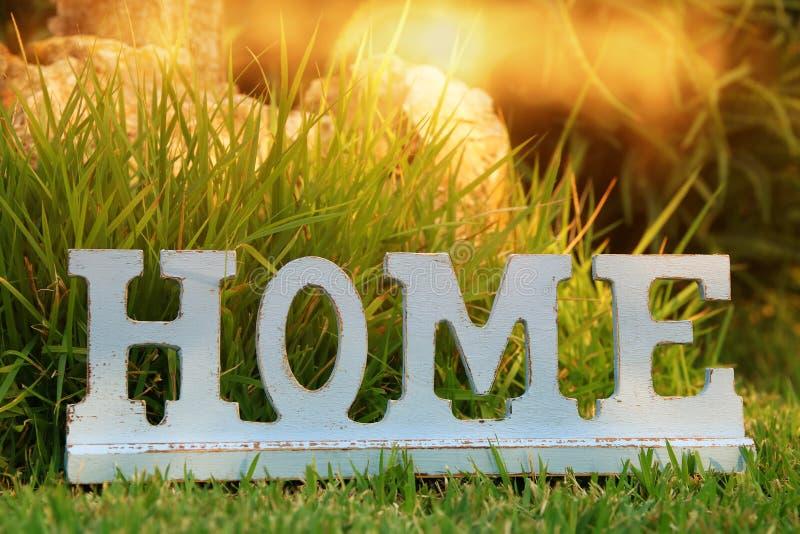 Tappningtecken med ordet HEM över grönt gräs utomhus royaltyfri bild