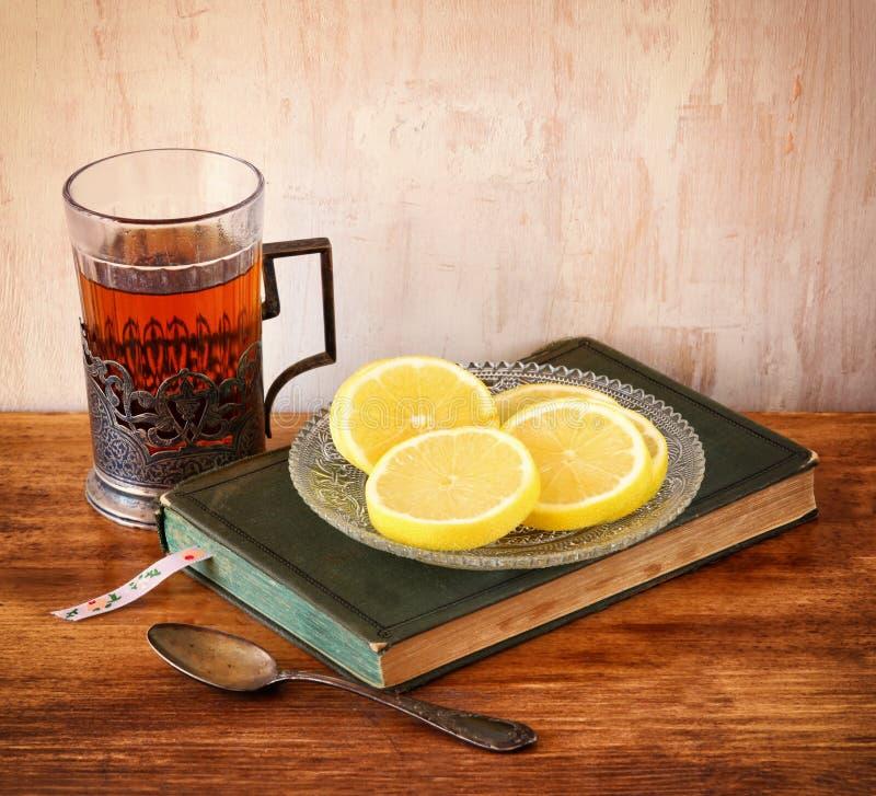 Tappningteexponeringsglas-hållare med nya citroner och den gamla boken över trätabellen retro filtrerad bild arkivfoton