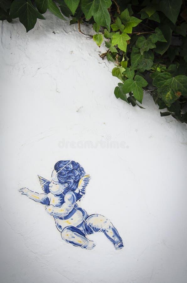 Tappningtegelplatta med ängel på den vita väggen fotografering för bildbyråer