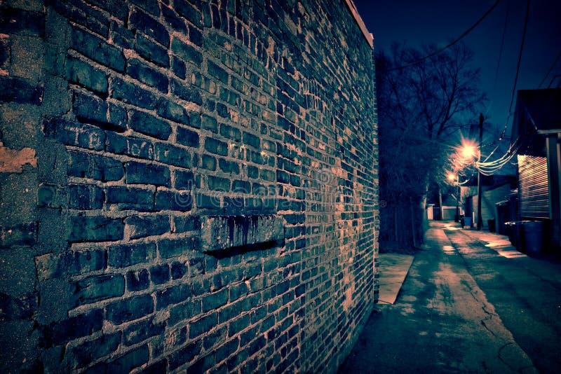 Tappningtegelstenvägg i ett mörker och våt Chicago gränd på natten fotografering för bildbyråer