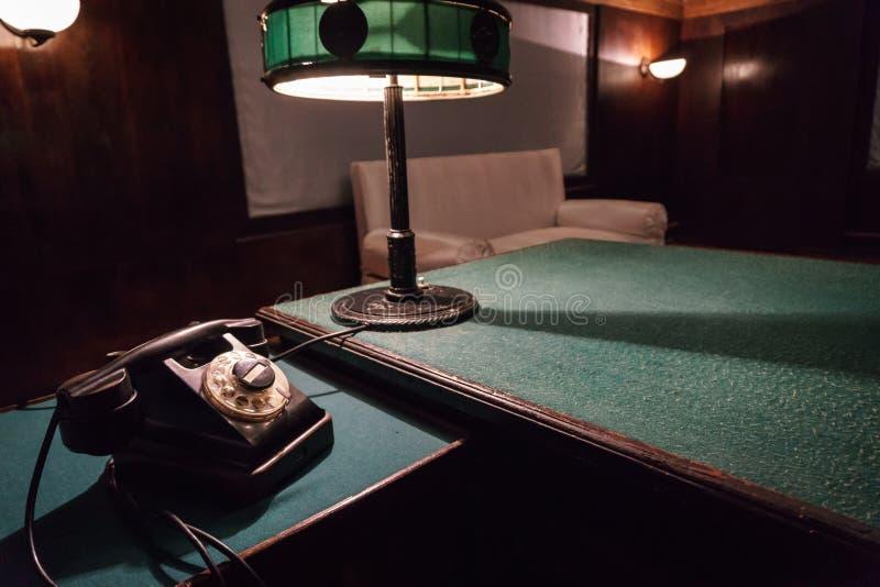 Tappningtelefon och läs- lampa på en tabell med den gröna torkduken royaltyfri foto