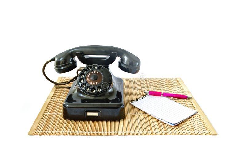 Tappningtelefon på rotting som är matt med rosa färgpennan och notepaden med copyspace royaltyfri fotografi