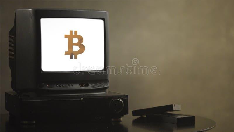 Tappningtelevision på den wood tabellen med bitcoin Gammal bitcoin för TVvisning Nära TV:N finns det den filmkassetter och videoe arkivfoto