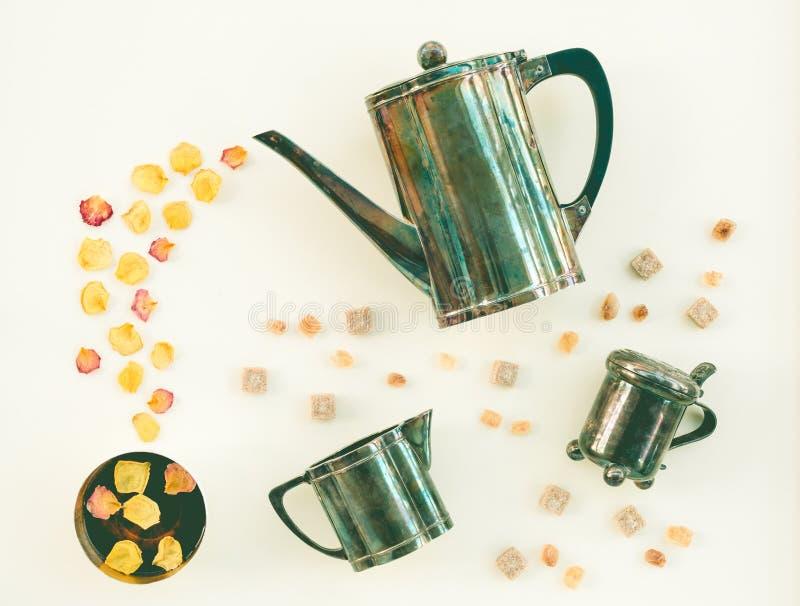 Tappningteservis och kopp te med rosa kronblad arkivfoton