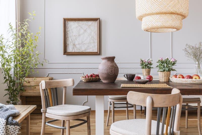 Tappningträstolar i vardagsrum med den långa tabellen med jordgubbar, äpplen, vasen och blommor på den, verkligt foto arkivfoton