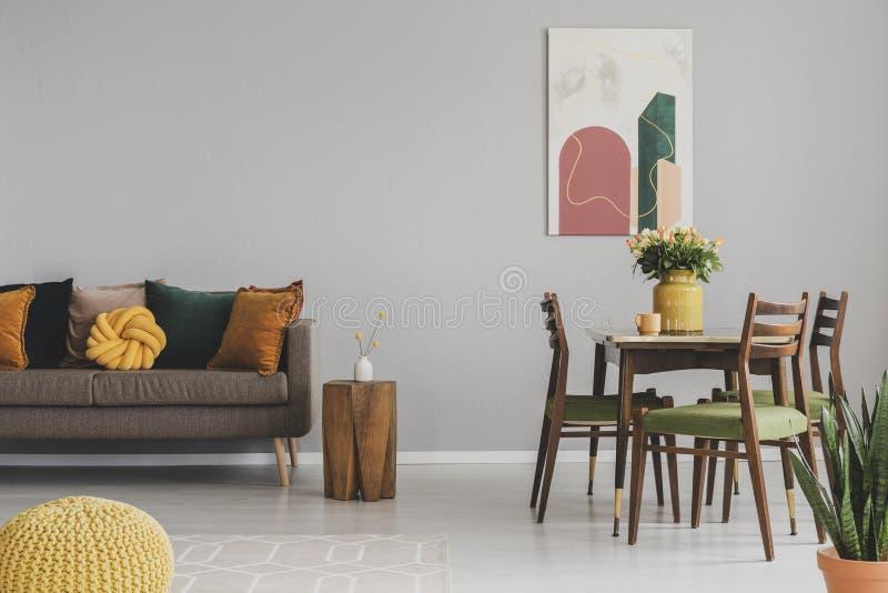 Tappninguppehälle och matsalinre med den retro tabellen med stolar och den bekväma soffan med kuddar arkivbild