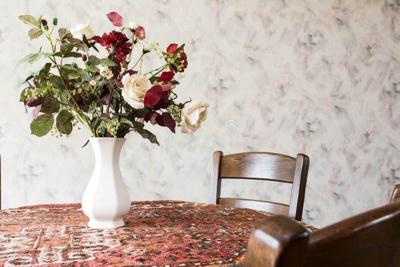 Tappningvardagsrum med den runda äta middag tabellen med blommor och modellen tapetserar royaltyfria bilder