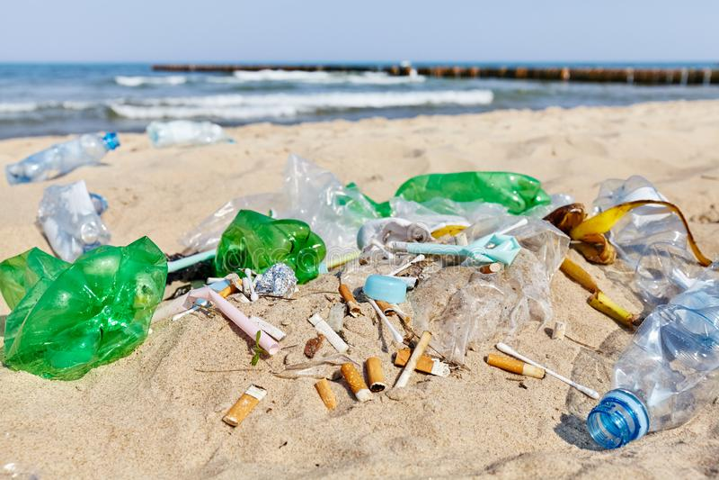 Tappo di bottiglia di plastica tra altri prodotti ed estremità di sigaretta monouso fotografia stock