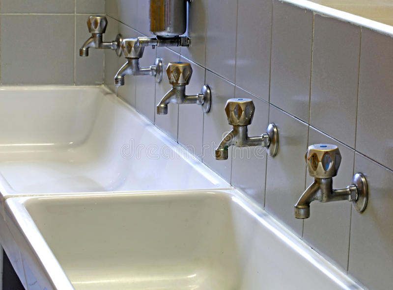 Taps in the ceramic sink of a bathroom of the school stock photos