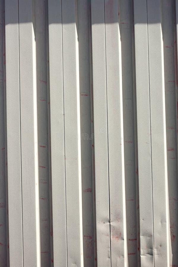 Tapume do metal branco estragado pela pintura vermelha imagens de stock royalty free