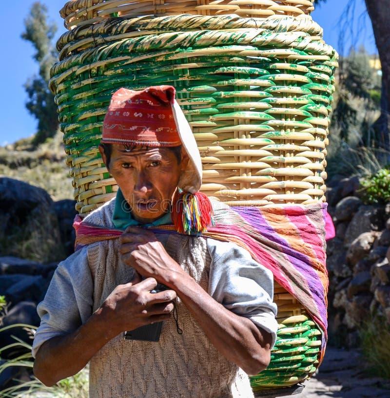 TAQUILE EILAND, PUNO, PERU 31 MEI, 2013: Niet geïdentificeerde enige mens in traditionele kleren die grote rotanmanden, op Taqu d royalty-vrije stock foto's