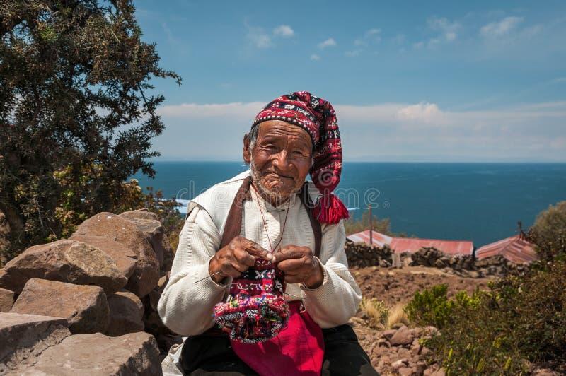 TAQUILE EILAND, PUNO, PERU - OKTOBER 13, 2016: Sluit omhoog portret van oude Peruviaanse mensen breiende hoed op de traditionele  royalty-vrije stock foto's