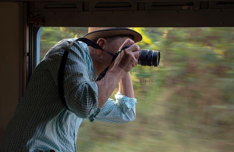 Tar den bärande hatten för den asiatiska fotografen med kameran bilder från det öppna fönstret av drevet royaltyfri bild