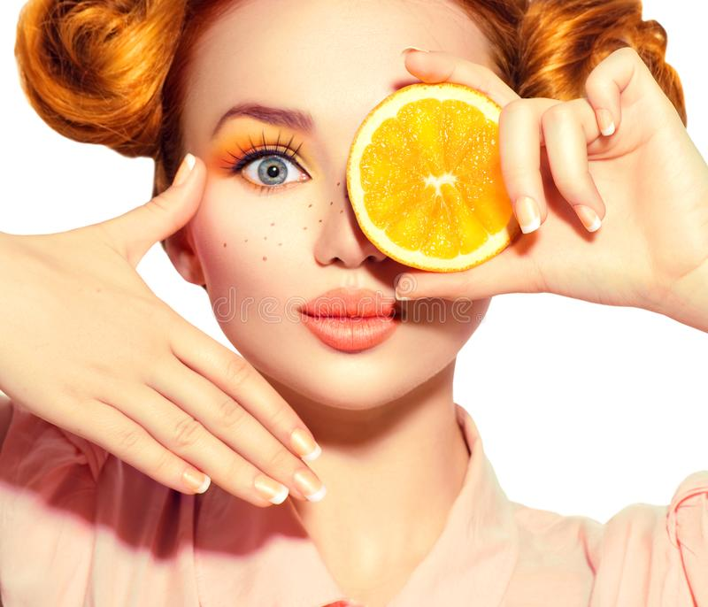 Tar den glade tonårs- flickan för skönhet saftiga apelsiner Den tonåriga modellflickan med fräknar, den roliga röda frisyren, gul arkivfoton
