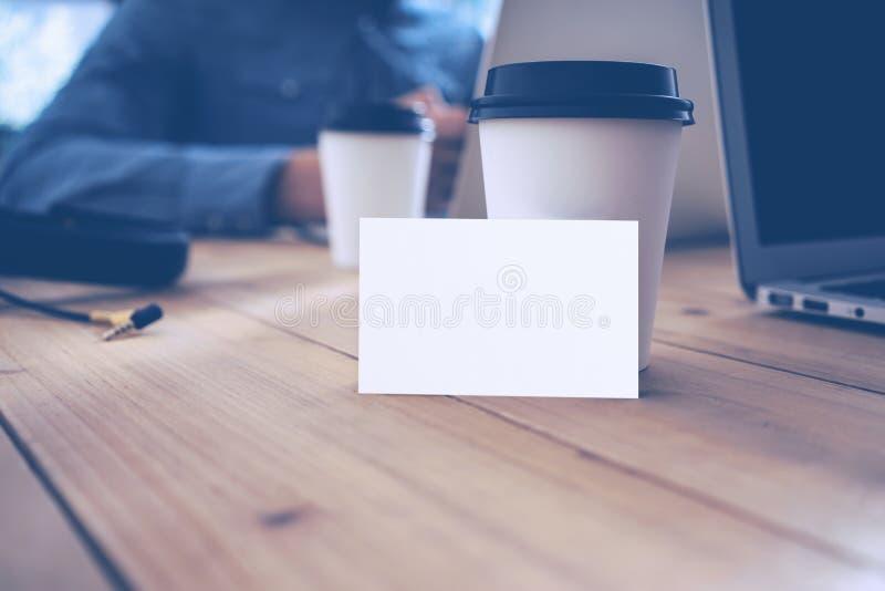 Tar den Wood tabellen för den tomma vita modellen för affärskortet den bort kaffekoppen Vuxet suddigt affärsmanWork Modern Notebo royaltyfri bild