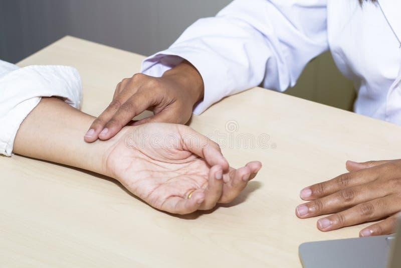 Tar den yrkesmässiga doktorn för handkvinnan pulsen med patienten på sjukhuset fotografering för bildbyråer