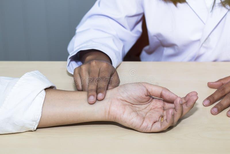 Tar den yrkesmässiga doktorn för handkvinnan pulsen med patienten på sjukhuset arkivfoton