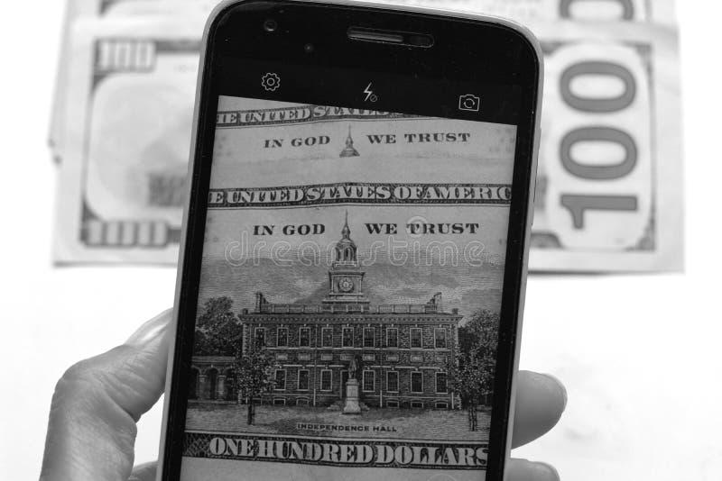 Tar dollar pengar bildsmartphonen royaltyfri bild