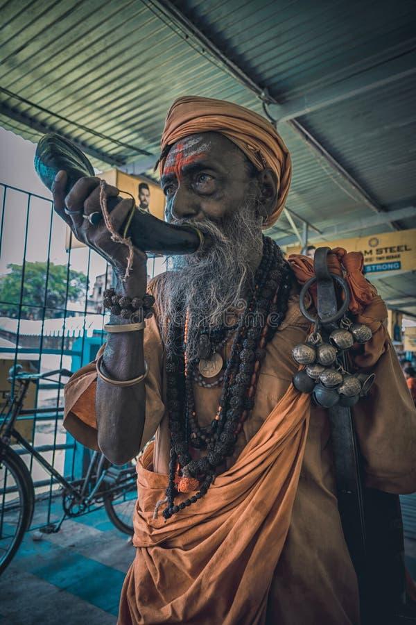 Tarakeswar, Indien - 21 april 2019. En oidentifierad Sadhu blåser kong vid Baba Taraknath Temple, ett hinduskt tempel hängivet gu royaltyfria bilder
