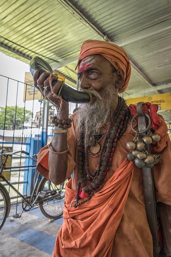 Tarakeswar, Indien - 21 april 2019. En oidentifierad Sadhu blåser kong vid Baba Taraknath Temple, ett hinduskt tempel hängivet gu arkivfoto