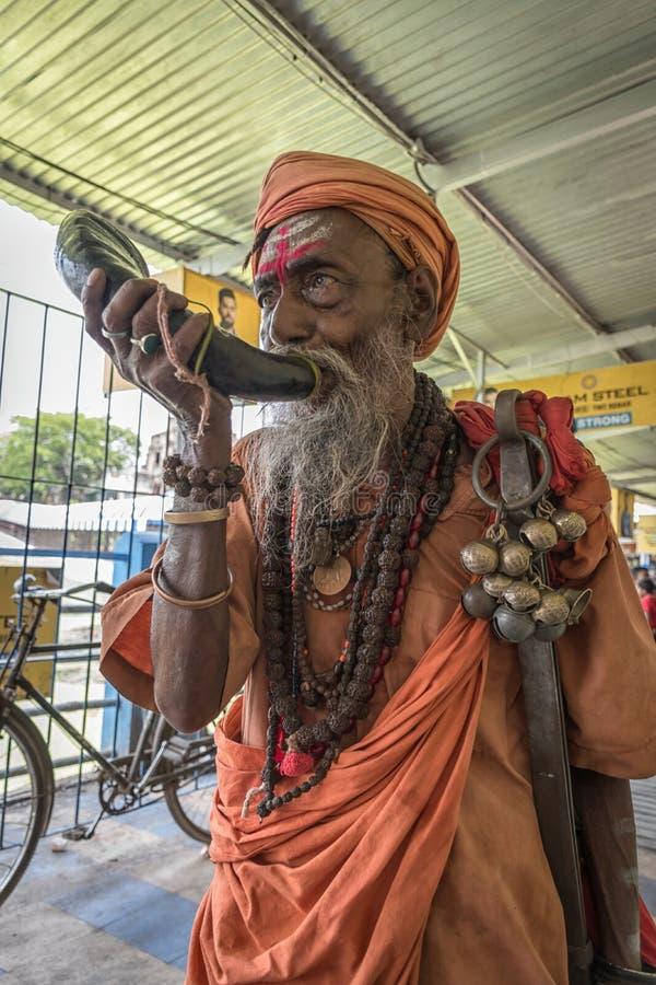 Tarakeswar, Indien - 21 april 2019. En oidentifierad Sadhu blåser kong vid Baba Taraknath Temple, ett hinduskt tempel hängivet gu arkivfoton