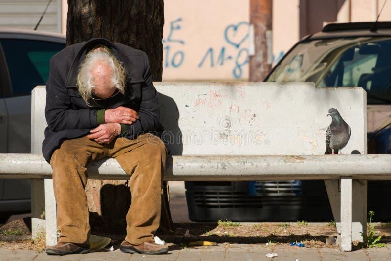 Taranto, Puglia/Italia - 03/23/2019: Un uomo anziano senza tetto perso depresso sul banco immagine stock libera da diritti