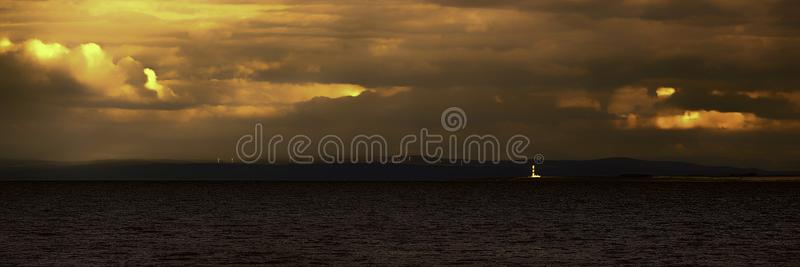 Tarbat Ness lighthouse lit up by late evening sunshine. Tarbat Ness lighthouse lit up in late evening summer sunset light with Rothes wind farm across the Moray royalty free stock images