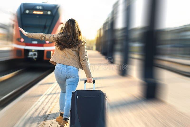 Tard du train Femme courant et chassant le train partant image stock