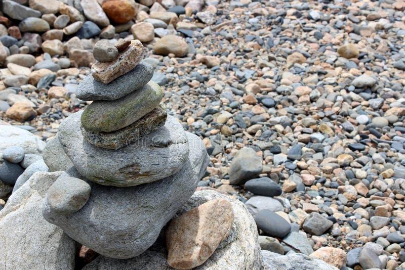 Tarde calma na praia com diversos tamanhos e formas das pedras equilibradas sobre se fotografia de stock