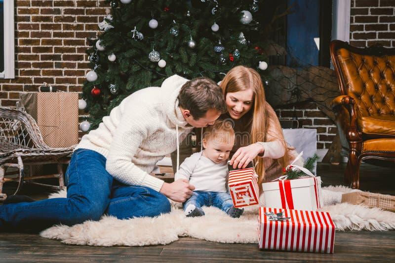 Tarde celebradora de la Navidad de la familia Gente caucásica de la familia tres que se sienta debajo del árbol de navidad del ár imagenes de archivo