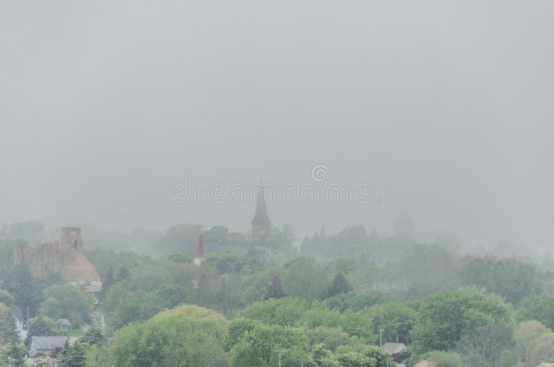 Tarde de niebla en una pequeña ciudad imagenes de archivo