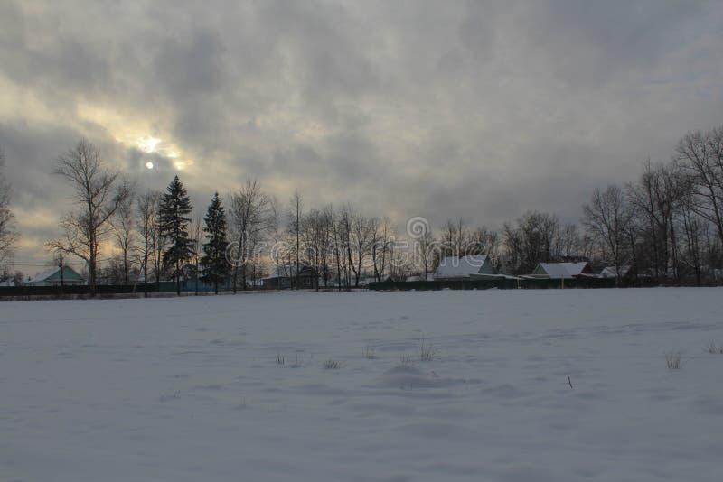 Tarde del invierno en el pueblo Los sistemas del sol, nubes, frío, oscuridad de la helada imagenes de archivo
