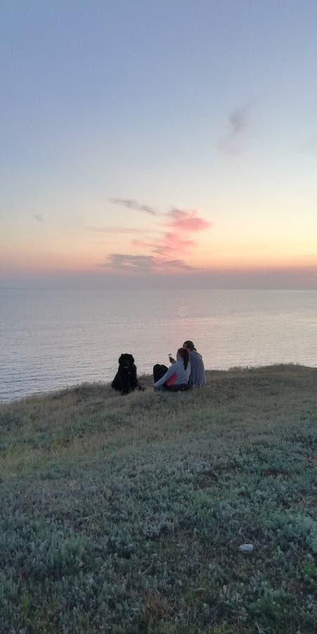 Tarde del verano Familia con un perro por el mar imagen de archivo libre de regalías