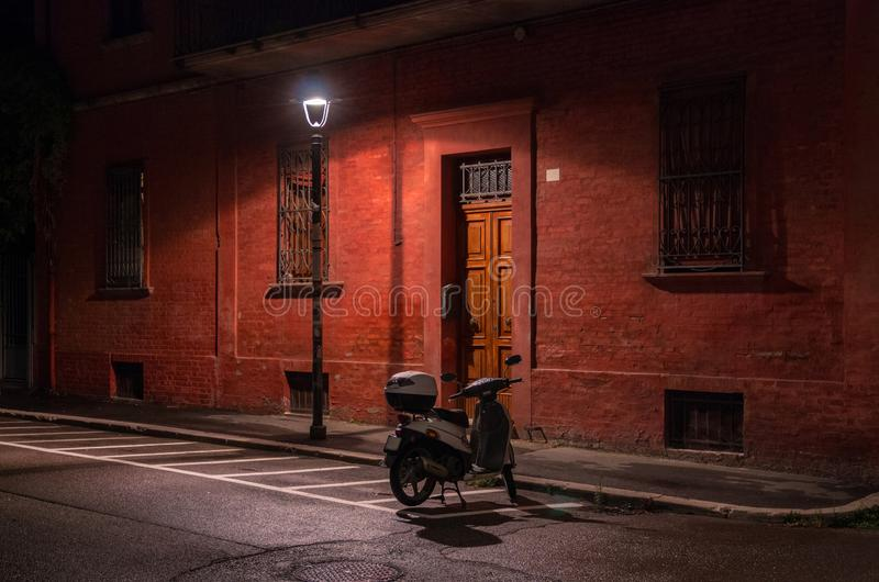 Tarde en la ciudad Vespa en el estacionamiento debajo de una lámpara de calle cerca del edificio rojo fotografía de archivo